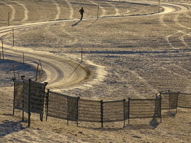 Ein Weg im Schnee, eine Person läuft in Richtung Sonne.