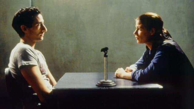 Eine Frau befragt einen Mann in einem Verhörungsraum.