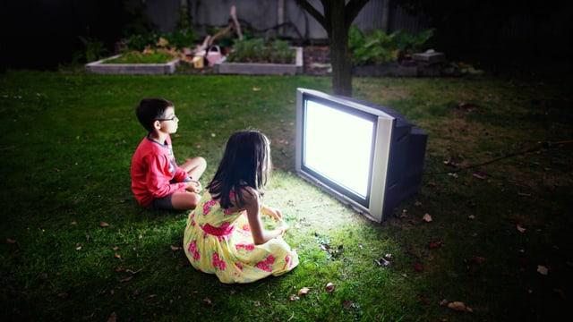 Zwei Kinder sitzen vor einem Fernseher auf einer Wiese
