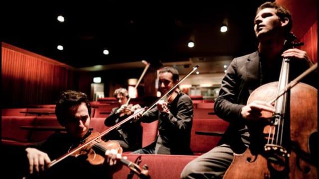 Die vier Bandmitgglieder in den Rängen eines Konzertsaals.