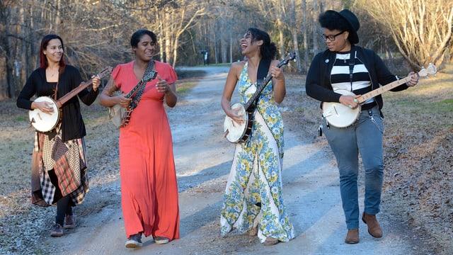 Vier Frauen in bunten Kleidern, jede mit einem Banjo, spielend, auf einem Feldweg