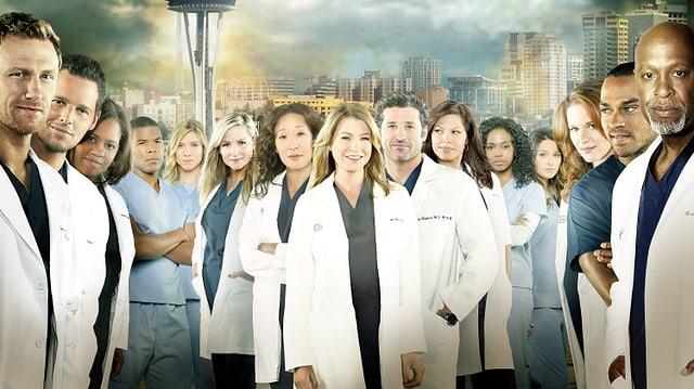 Eine Gruppe von Menschen in Ärztekitteln. Im Hintergrund ist eine Stadt erkennbar.