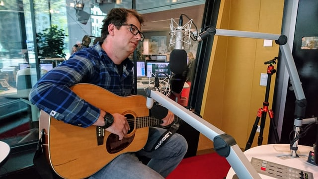 Curdin Nicolay sesa cun sia ghitarra en il studio.