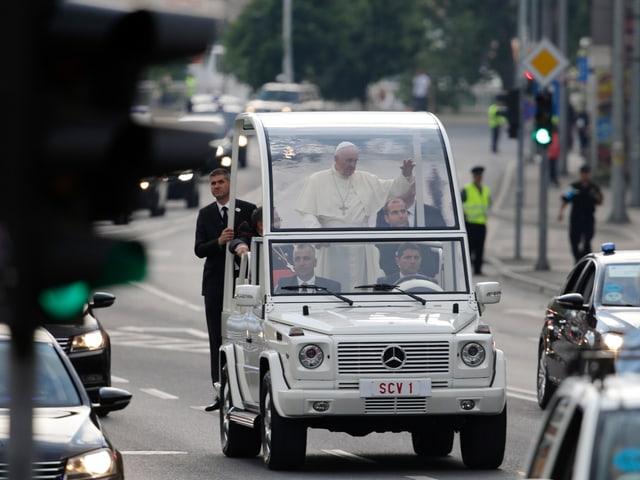 Das Papamobil mit Papst Franziskus auf einer Strasse.