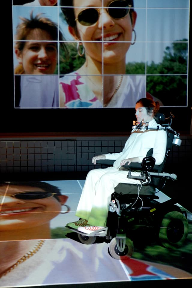 Eine Frau in einem Rollstuhl vor einer Leinwand, die ein lachendes junges Mädchen mit Sonnenbrille zeigt.