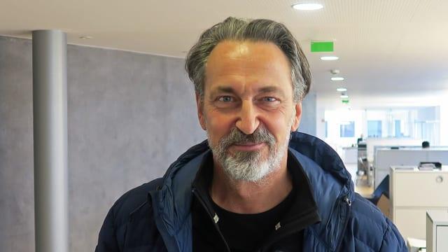 Porträtbild eines älteren Mannes mit grau-melierten Haaren und einem Dreitagebart