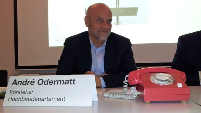 Stadtrat André Odermatt an der Pressekonferenz vor einem roten Telefon.