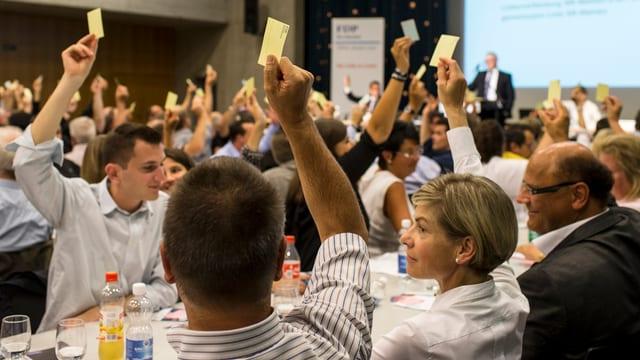 Politiker sitzen an Tischen und heben für eine Abstimmung gelbe Zettel hoch.