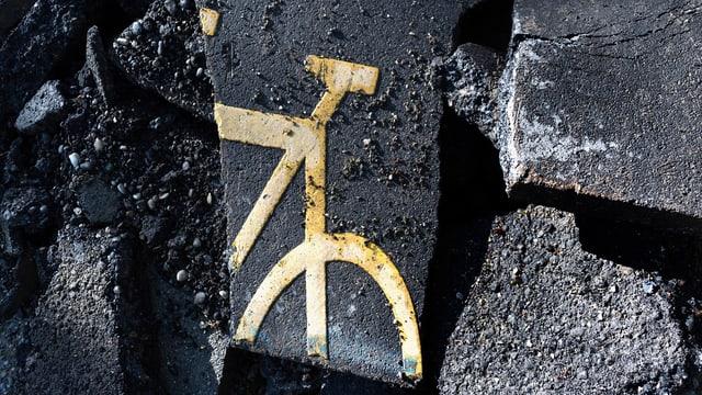 teilstück eines Fahrradzeichens auf einem aufgebrochenen Trottoir