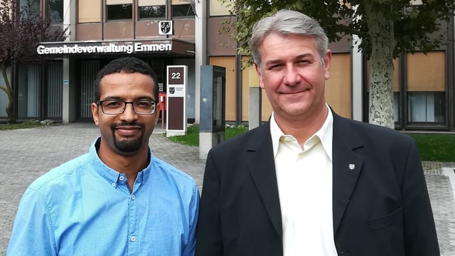 Zwei Männer vor einem Verwaltungsgebäude.