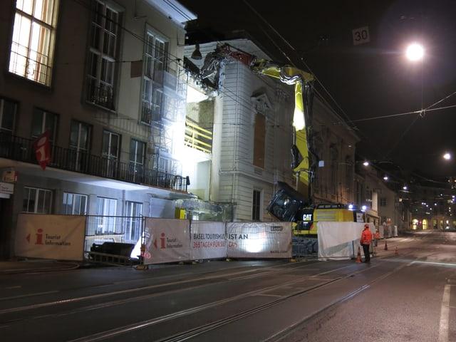 Bagger reisst in der Nacht den Eingang des Stadtcasinos ab. Davor stehen ein paar Bauarbeiter.