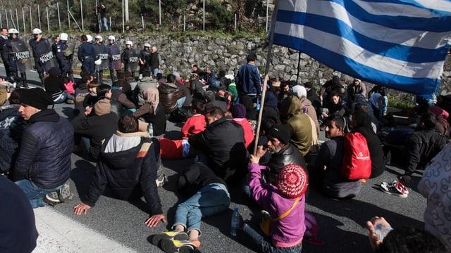 fugitivs che spetgan cun ina bandiera da la Grezia avant ina barricada da la polizia