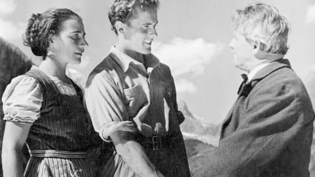 Filmausschnitt. Der Protagonist mit seiner Frau im Hintergrund schüttelt die Hand eines älteren Mannes.