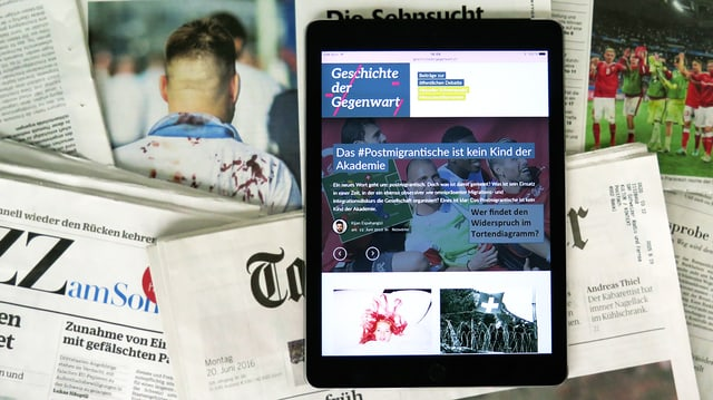 Die Homepage von «Geschichte der Gegenwart» auf einem iPad vor dem Hintergrund von verschiedenen Zeitungen.