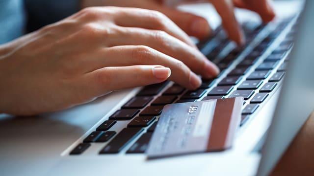 Eine Frau am PC, auf der Tastatur liegt eine Kreditkarte.