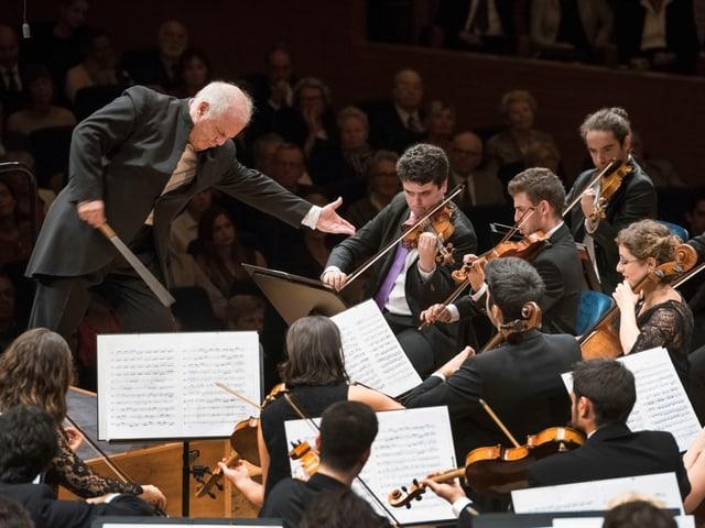 Das Bild zeigt einen Ausschnitt des Orchesters und den Dirigenten; es ist vom hinteren Teil der Bühne aus aufgenommen. Die Blickrichtung ist leicht erhöht. Wir sehen die vorderen beiden Pulte der ersten Geigen, der Celli und der Bratschen; den Dirigenten, und im Hintergrund das Publikum. Die Musikerinnen und Musiker schauen konzentriert in ihre Noten, die Bögen sind auf den Instrumenten, sie spielen gerade. Der Dirigent dirigiert ohne Noten. Er steht breitbeinig auf seinem Podest, geht leicht in die Knie und beugt sich in Richtung der ersten Geigen. Im Zentrum des Bildes ist seine linke Hand: sie zeigt ausgestreckt auf die ersten Geigen, mit einer Geste, die mehr Klang von den Geigen fordert.