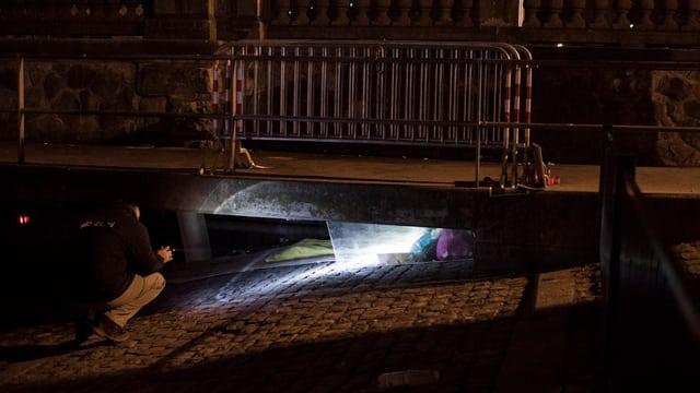 Ein Mitarbeiter der Stadt schaut in einen Schacht, um zu schauen,ob darin ein Obdachloser schläft.