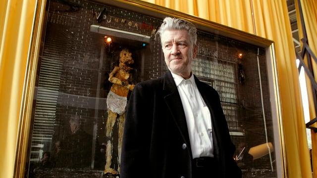 David Lynch posiert vor einem seiner Gemälde.