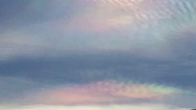 Perlmutfarbene Wolken neben der Sonne.