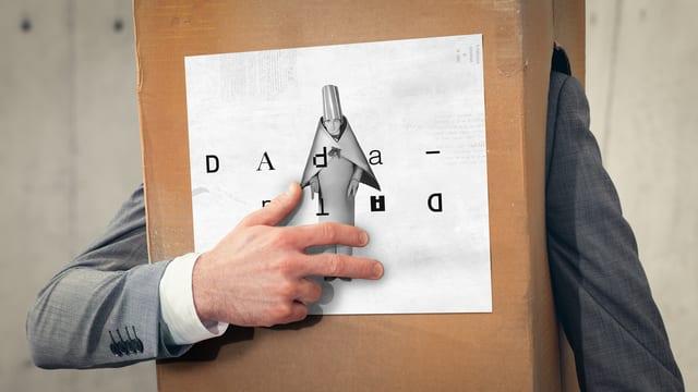 Mann in einem Pappkarton legt drei Finger aufs Herz.