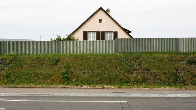Man sieht ein Haus hinter einer Lärmschutzwand direkt an der Autobahn.