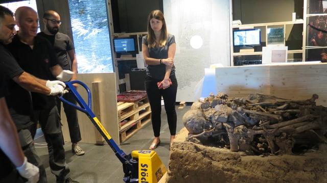 Drei Umzugsspezialisten verschieben ein jungsteinzeitliches Grab auf einem Hebegerät.