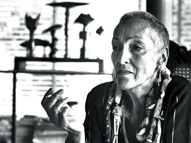 Meret Oppenheim in ihrer Wohnung, nachdenklich, rauchend.