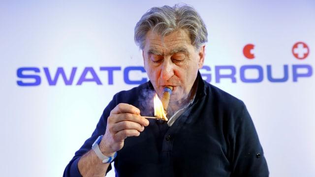 Swatch-Chef Nick Hayek zündet sich eine Zigarre an.