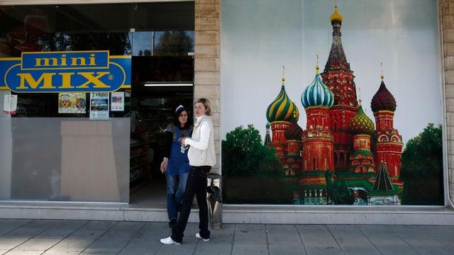 Zwei Frauen stehen vor einem Laden. Dort hängt ein Bild des Kremls.
