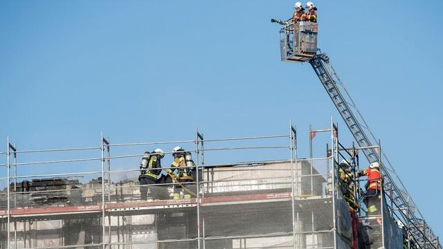 Feuerwehrmänner auf einem Dach. Drehleiter mit Korb.