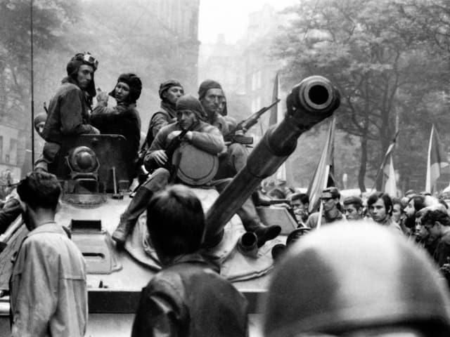 Panzer in einer Menschenmenge, darauf sitzen Soldaten