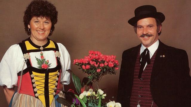 Jodlerin und Jodler in ihren Trachten links und rechts von einem Blumen-Arrangement.