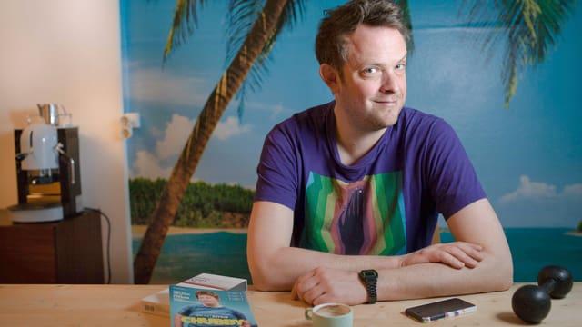 Regisseur Bruno Deville sitzt an einem Tisch und schaut seitwärts in die Kamera.