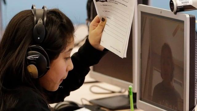 Eine junge Frau vor einem Computerbildschirm mit Webcam