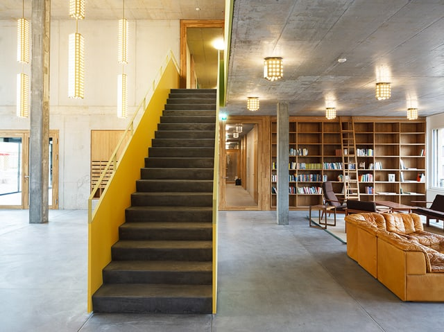 Grosse Betonhalle mit Treppe und Büchergestell.