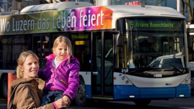 Frau mit Kind vor Bus
