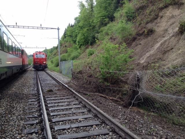 Zwei stehende Züge bei einem bis zum Geleise abgerutschten Hang.