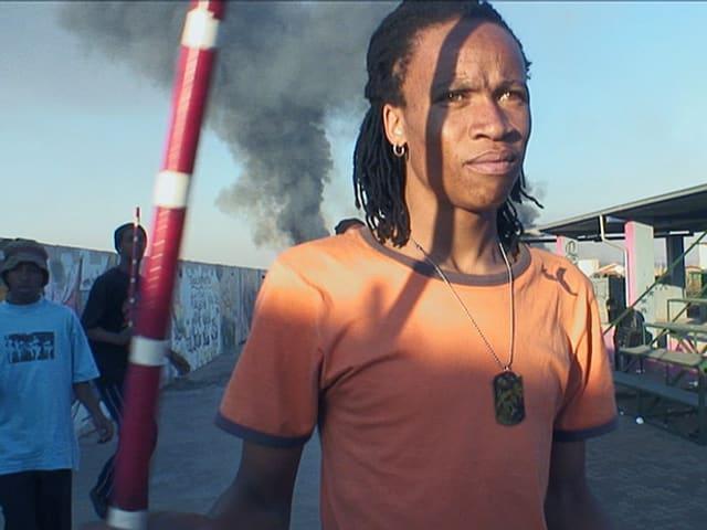 Ein Mann mit orangefarbenem T-Shirt steht auf der Strasse, im Hintergrund steigt grauer Rauch gegen den Himmel.