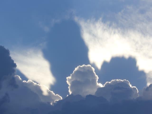 Eine Quellwolke wirft einen viel grösseren Schatten auf eine andere Wolke dahinter.