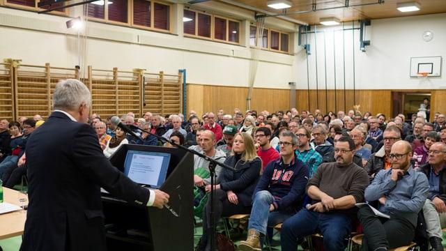 Blick auf eine Gemeindeversammlung in einer Turnhallen.