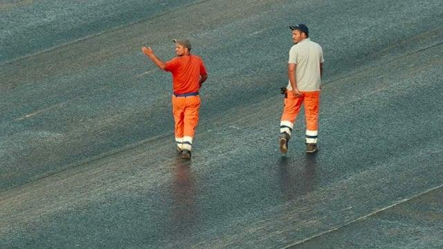 Zwei Bauarbeiter, der eine kratzt sich im Schritt.
