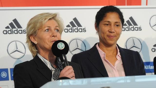 Silvia Neid spricht während einer PK ins Mikrofon, daneben steht ihre Nachfolgerin Steffi Jones.