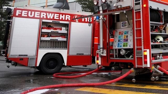 Feuerwehrfahrzeuge mit Schlauch im Einsatz