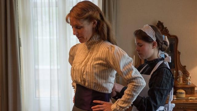 Lisa-Maria schnürt der Fabrikantengattin die Kleider am Rücken zu