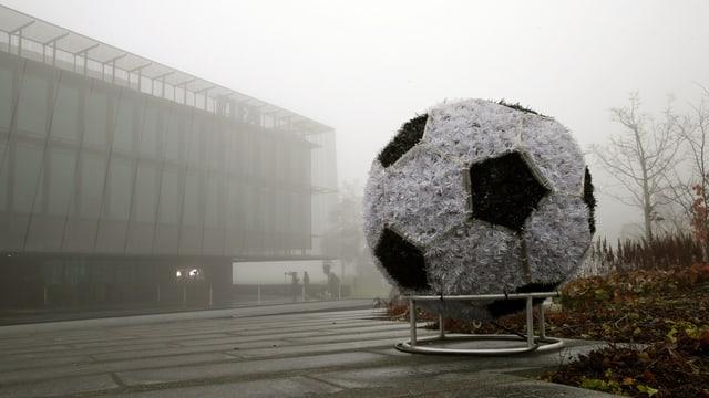 Übergrosser Fussball vor Bürogebäude im Nebel