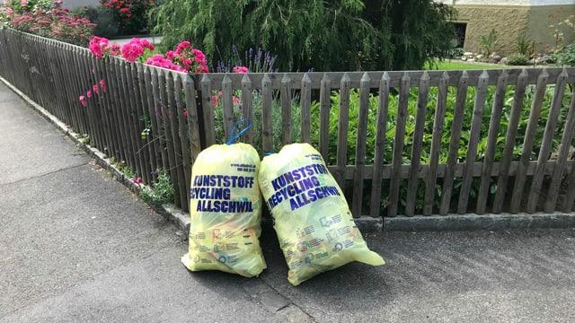 Zwei Abfallsäcke mit der Aufschrift: Kunststoff-Recycling Allschwil