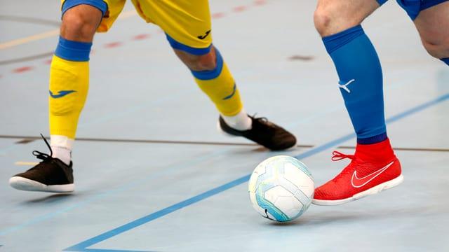 Beine und Füsse von Fussballspielern und Ball