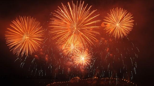 Feuerwerk erhellt den Nachthimmel orange und rot.