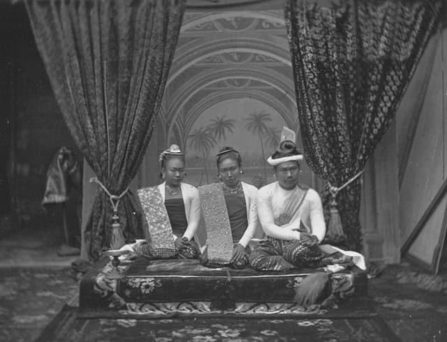 Foto von zwei Frauen und dem burmesischen König auf einer Erhöhung, hinten Vorhänge.