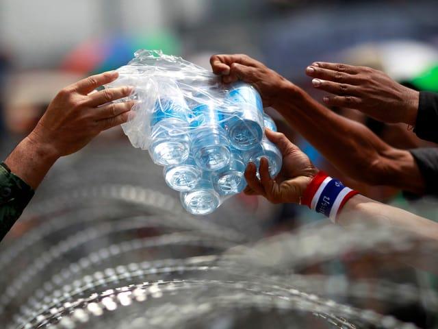 Ein Soldat gibt Demonstranten Wasserflaschen.